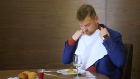 Hombre de negocios que toma la servilleta blanca antes de comer durante almuerzo en restaurante gastrónomo almacen de video
