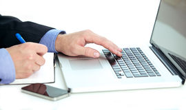Hombre de negocios que toma notas de una computadora portátil Imagenes de archivo
