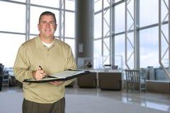 Hombre de negocios que toma notas en pasillo Imágenes de archivo libres de regalías