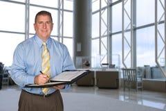 Hombre de negocios que toma notas en pasillo Imagenes de archivo