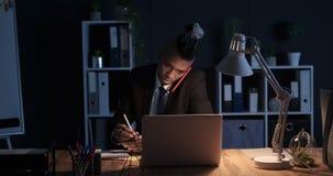 Hombre de negocios que toma notas mientras que habla en el teléfono móvil en la oficina de la noche