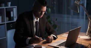 Hombre de negocios que toma notas mientras que trabaja en la oficina de la noche