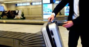 Hombre de negocios que toma su equipaje del carrusel del equipaje almacen de video