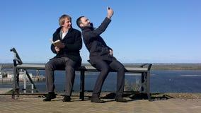 Hombre de negocios que toma un selfie con un teléfono elegante al aire libre Fotografía de archivo