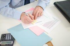 Hombre de negocios que toma una nota sobre un post-it Foto de archivo libre de regalías