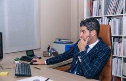 Hombre de negocios que trabaja con el ordenador en la oficina Imagen de archivo libre de regalías