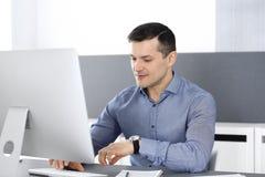 Hombre de negocios que trabaja con el ordenador en oficina moderna Headshot del empresario o del director de empresa de sexo masc imágenes de archivo libres de regalías