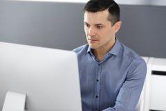 Hombre de negocios que trabaja con el ordenador en oficina moderna Headshot del empresario o del director de empresa de sexo masc imagen de archivo libre de regalías