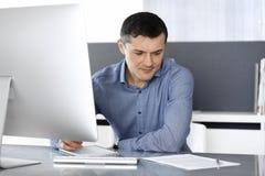 Hombre de negocios que trabaja con el ordenador en oficina moderna Headshot del empresario o del director de empresa de sexo masc imagenes de archivo