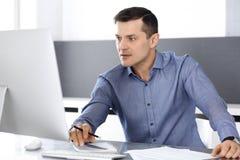 Hombre de negocios que trabaja con el ordenador en oficina moderna Headshot del empresario o del director de empresa de sexo masc fotografía de archivo