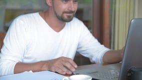 Hombre de negocios que trabaja con el ordenador portátil mientras que lee un libro de planificación y piensa idea almacen de metraje de vídeo