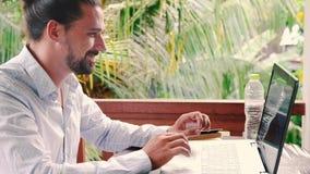 Hombre de negocios que trabaja con el ordenador portátil mientras que lee un libro de planificación y piensa idea almacen de video