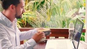 Hombre de negocios que trabaja con el ordenador portátil mientras que lee un libro de planificación y piensa idea metrajes