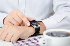 Hombre de negocios que trabaja con el reloj elegante en restaurante Fotos de archivo libres de regalías