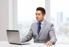 Hombre de negocios que trabaja con la computadora portátil en oficina Foto de archivo libre de regalías