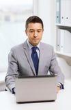 Hombre de negocios que trabaja con la computadora portátil en oficina Imagenes de archivo
