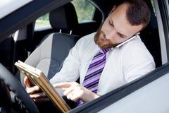 Hombre de negocios que trabaja con la tableta y el teléfono en coche Imagen de archivo