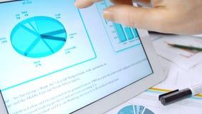 Hombre de negocios que trabaja con los diagramas y la tableta