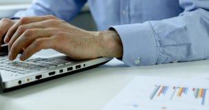 Hombre de negocios que trabaja en cartas de los datos financieros en la oficina almacen de video