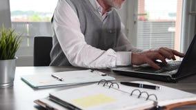 Hombre de negocios que trabaja en el documento y que mecanograf?a en el ordenador port?til almacen de video
