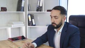Hombre de negocios que trabaja en el escritorio de oficina con la pantalla verde elegante del teléfono, de la tableta y del orden metrajes