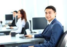 Hombre de negocios que trabaja en el ordenador en la oficina con sus colegas Imagen de archivo libre de regalías