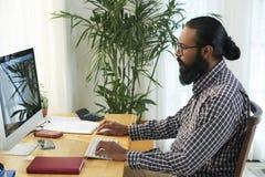 Hombre de negocios que trabaja en el ordenador en la oficina fotos de archivo