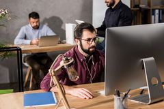 hombre de negocios que trabaja en el ordenador en oficina y música que escucha imágenes de archivo libres de regalías