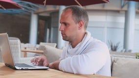 Hombre de negocios que trabaja en el ordenador portátil en café almacen de metraje de vídeo