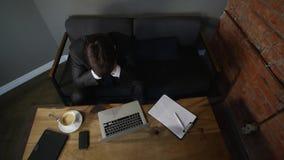Hombre de negocios que trabaja en el ordenador portátil en café el hombre de negocios está trastornado Visión superior metrajes