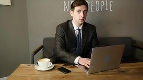 Hombre de negocios que trabaja en el ordenador portátil en café mirada referida miradas del hombre joven metrajes