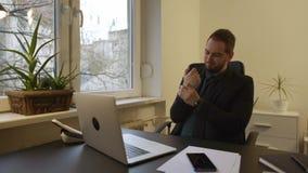 hombre de negocios que trabaja en el ordenador portátil en dolor de la muñeca de la oficina almacen de video