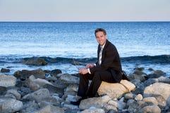 Hombre de negocios que trabaja en el ordenador portátil en la playa Imagenes de archivo