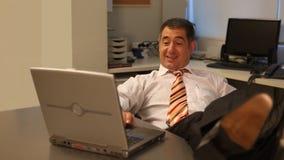 Hombre de negocios que trabaja en el ordenador portátil en oficina metrajes