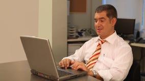 Hombre de negocios que trabaja en el ordenador portátil en oficina almacen de metraje de vídeo