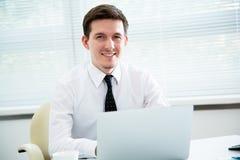Hombre de negocios que trabaja en el ordenador portátil en oficina Imágenes de archivo libres de regalías