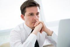 Hombre de negocios que trabaja en el ordenador portátil en oficina Foto de archivo libre de regalías