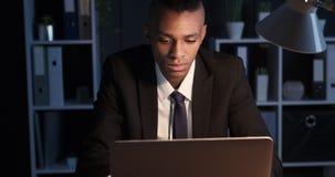 Hombre de negocios que trabaja en el ordenador portátil en la noche almacen de video