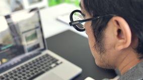 Hombre de negocios que trabaja en el ordenador portátil en la oficina, lente que lleva asiática del hombre de negocios de la cáma almacen de metraje de vídeo