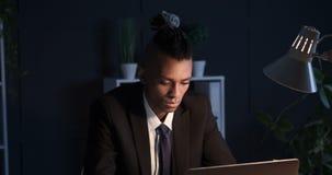Hombre de negocios que trabaja en el ordenador portátil de la oficina en noche almacen de video