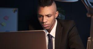 Hombre de negocios que trabaja en el ordenador portátil en la oficina de la noche