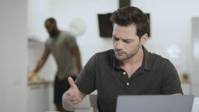 Hombre de negocios que trabaja en el ordenador portátil en el lugar de trabajo remoto Tabla de limpieza del hombre negro metrajes