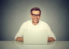 Hombre de negocios que trabaja en el ordenador portátil, sonriendo imagenes de archivo