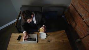 Hombre de negocios que trabaja en el ordenador portátil y el café de consumición en el café Visión superior almacen de metraje de vídeo