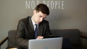 Hombre de negocios que trabaja en el ordenador portátil y documentos en café almacen de metraje de vídeo