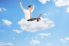 Hombre de negocios que trabaja en el ordenador portátil y que gesticula la felicidad asentada encendido Imagen de archivo libre de regalías