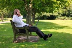 Hombre de negocios que trabaja en el parque Fotografía de archivo