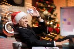 Hombre de negocios que trabaja en el ` s Eve del Año Nuevo Él engaña alrededor y lanza trozos de papel Imagen de archivo libre de regalías