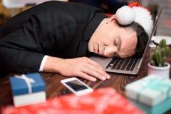 Hombre de negocios que trabaja en el ` s Eve del Año Nuevo Él estaba muy cansado y se cayó dormido detrás de su ordenador portáti Fotografía de archivo