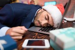 Hombre de negocios que trabaja en el ` s Eve del Año Nuevo Él estaba muy cansado y se cayó dormido detrás de su ordenador portáti Imagen de archivo libre de regalías